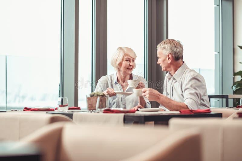 有吸引力的退休的夫妇吃早餐在咖啡馆一起 图库摄影