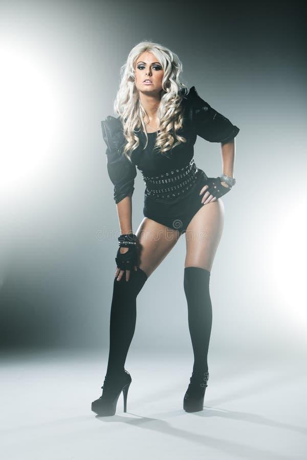 有吸引力的高档时尚黑色的金发碧眼的女人穿衣与长袜 库存照片
