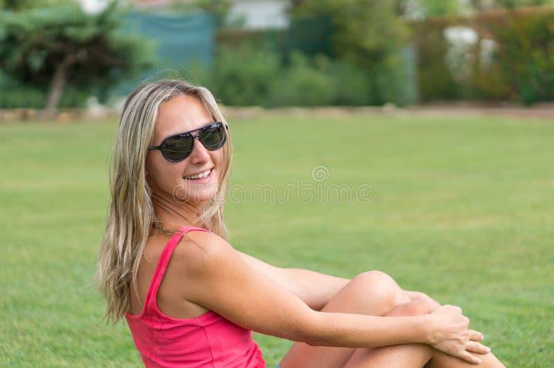 有吸引力的年轻人微笑的美丽的卷曲金发亭亭玉立的女孩塑造在摆在桃红色的T恤杉的画象看起来去镇静神色,  免版税库存图片