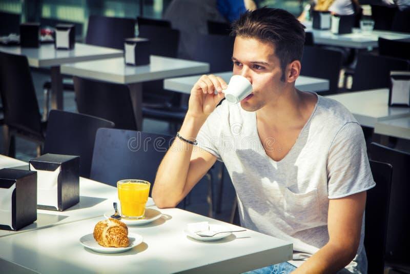 有吸引力的年轻人s早餐,饮用的咖啡 免版税库存照片