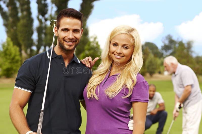 有吸引力的年轻夫妇准备好打高尔夫球 免版税库存图片