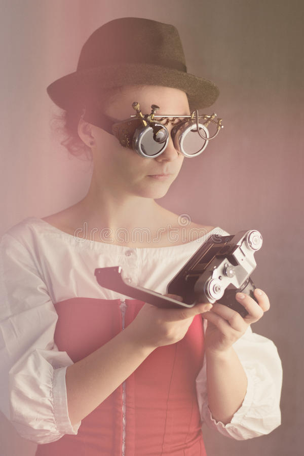 有吸引力的steampunk女孩举行照相机 库存图片