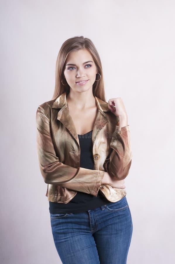 有吸引力美好的年轻人相当时髦摆在的夫人的时尚夹克和牛仔裤演播室 库存照片