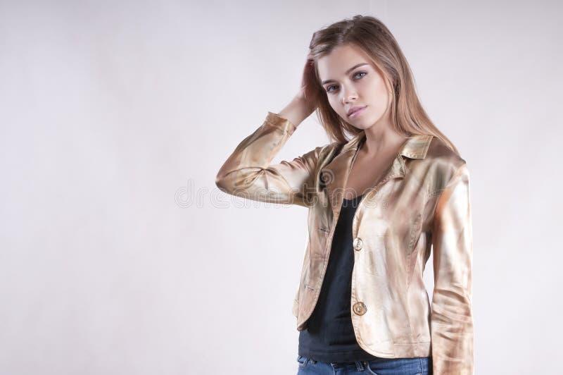 有吸引力美好的年轻俏丽的女孩的时尚夹克和牛仔裤演播室 库存图片