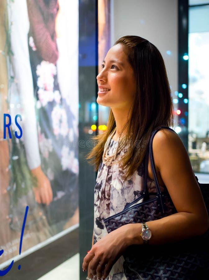 有吸引力,时髦,时兴的年轻亚洲妇女窗口购物 免版税库存照片