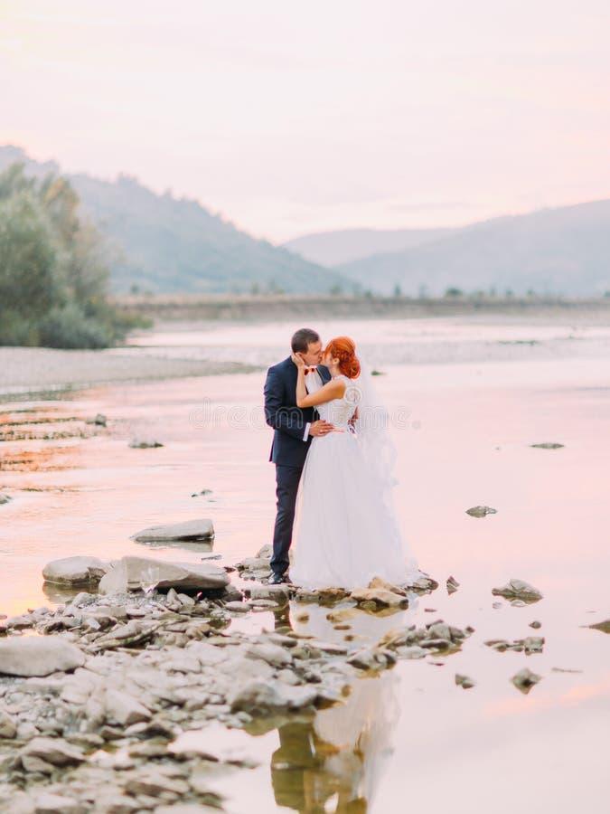 有吸引力年轻婚礼夫妇亲吻 一条山河的岸有石头的在背景 免版税库存图片