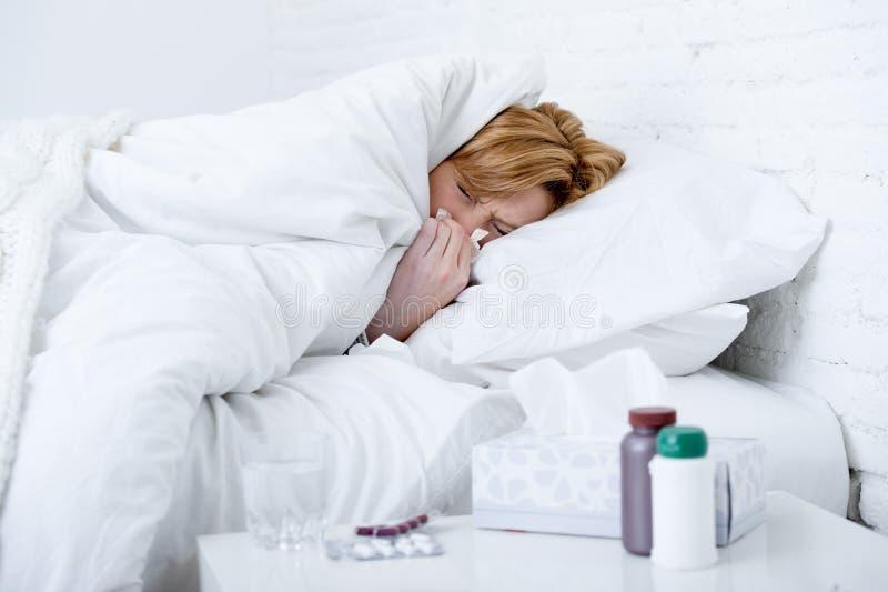 有吹在遭受冷的流感病毒症状的床上的组织的打喷嚏的鼻子的妇女有医学压片药片 库存照片