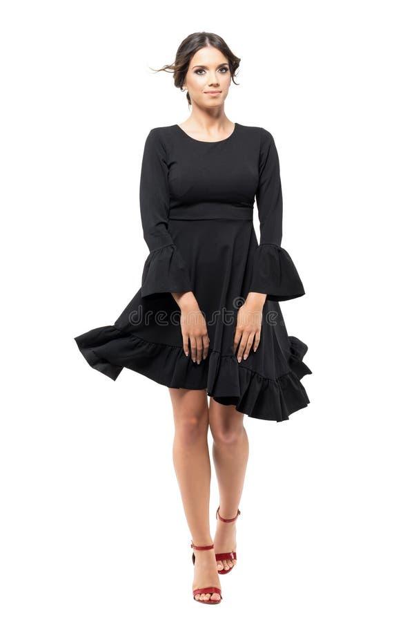 有吹的风的妇女走的前面藏品黑色飞行礼服在头发和衣裳 图库摄影