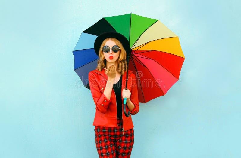 有吹红色嘴唇的五颜六色的伞的时髦的年轻女人送甜空气亲吻,佩带的红色夹克,在蓝色墙壁上的黑帽会议 免版税库存图片