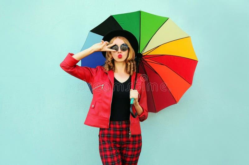 有吹红色嘴唇的五颜六色的伞的时髦的年轻女人送甜空气亲吻,佩带的红色夹克,在蓝色墙壁上的黑帽会议 免版税图库摄影