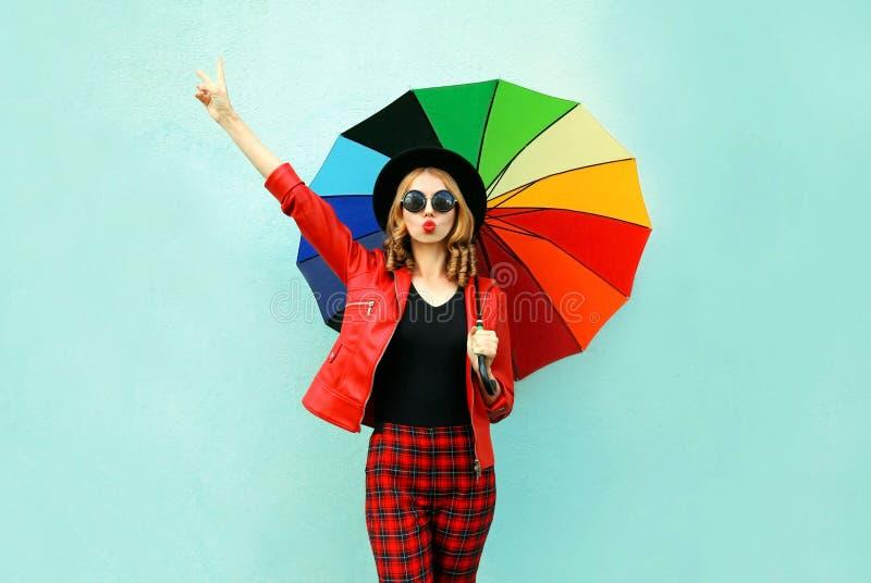 有吹红色嘴唇的五颜六色的伞的时髦的年轻女人送甜空气亲吻,佩带的红色夹克,在蓝色墙壁上的黑帽会议 库存照片