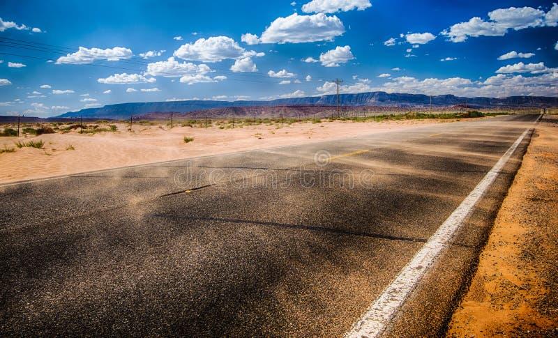 有吹红色沙子的阵风的黑沥青高速公路在亚利桑那北部沙漠 库存图片