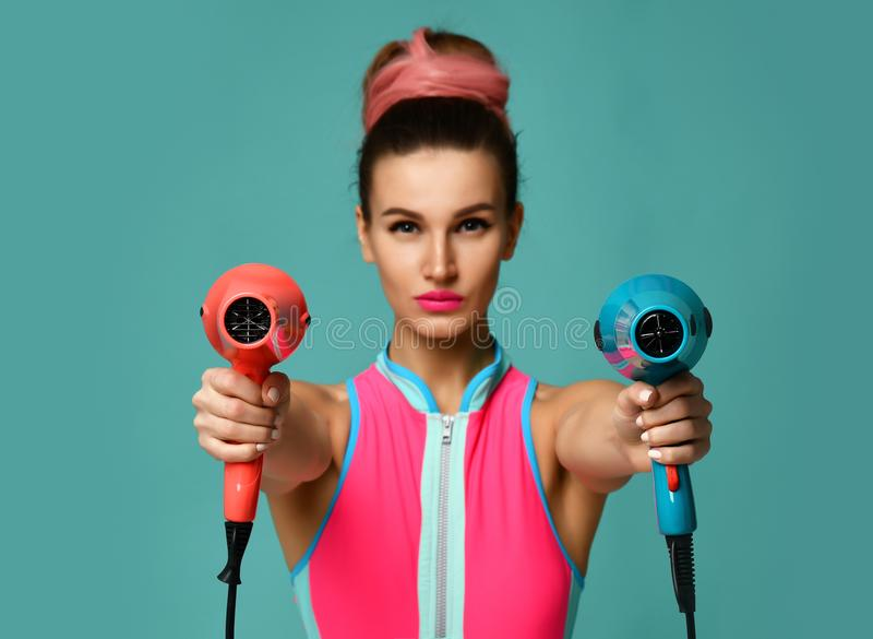 有吹风器的愉快的年轻深色的妇女在蓝色薄荷的背景 免版税库存图片