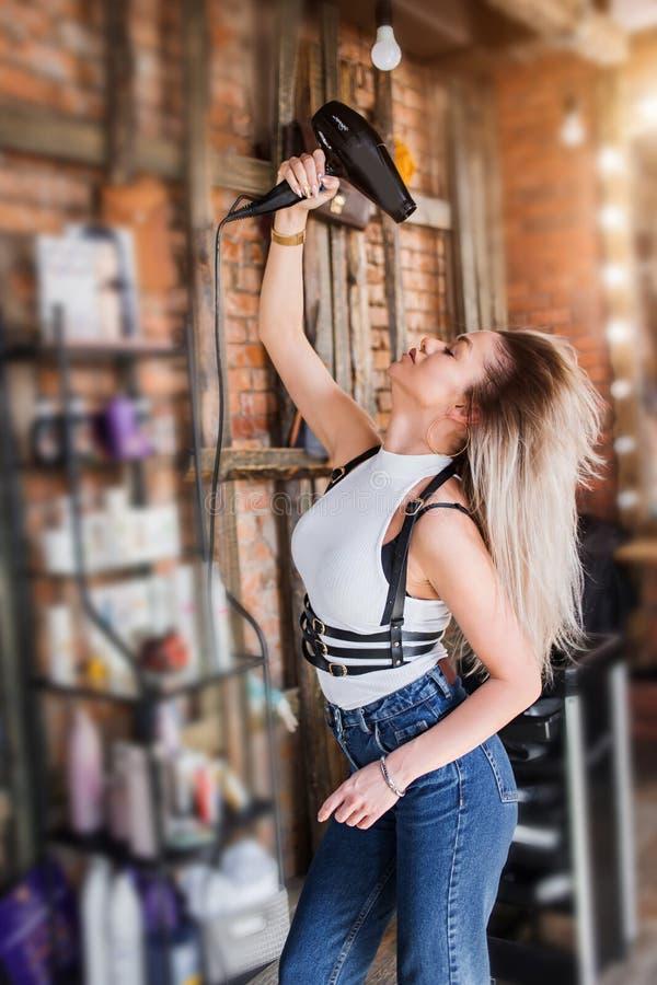 有吹风器的美丽的女孩 免版税图库摄影