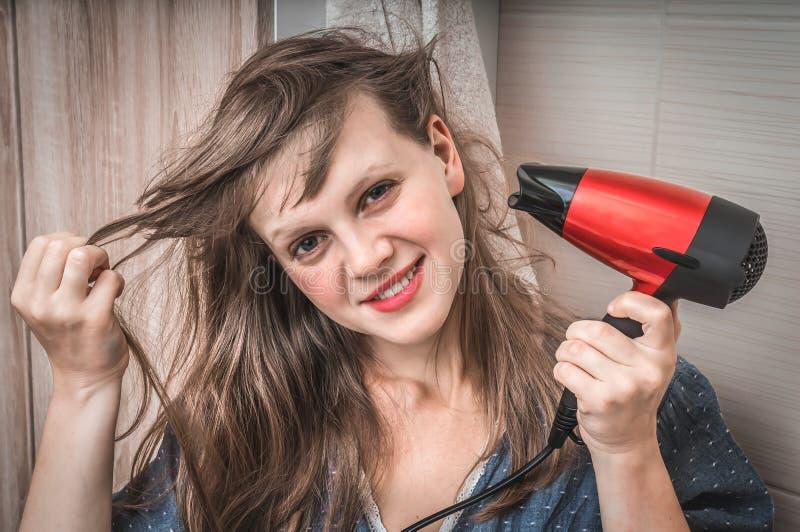 有吹风机的时尚女孩烘干她的头发 库存图片