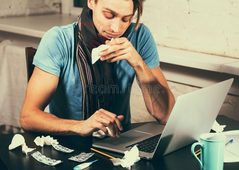 有吹他的在他的客厅运转的笔记本的温度计病残的年轻人鼻子 免版税库存图片