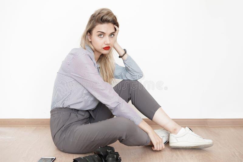 有周道地看照相机的明亮的嘴唇的年轻性感的金发碧眼的女人,当坐演播室、神色和情感的地板,时 免版税图库摄影