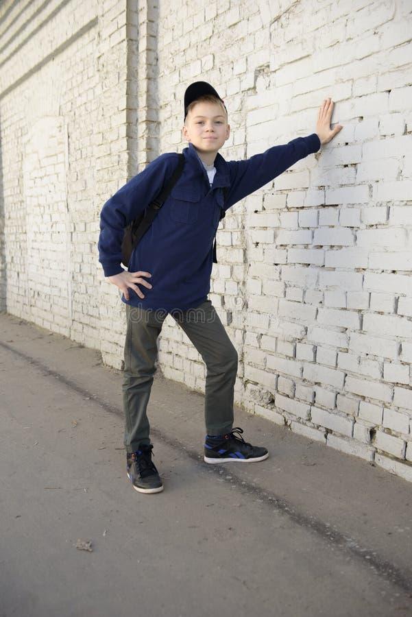 有周道的神色的少年 背景砖墙 免版税库存图片