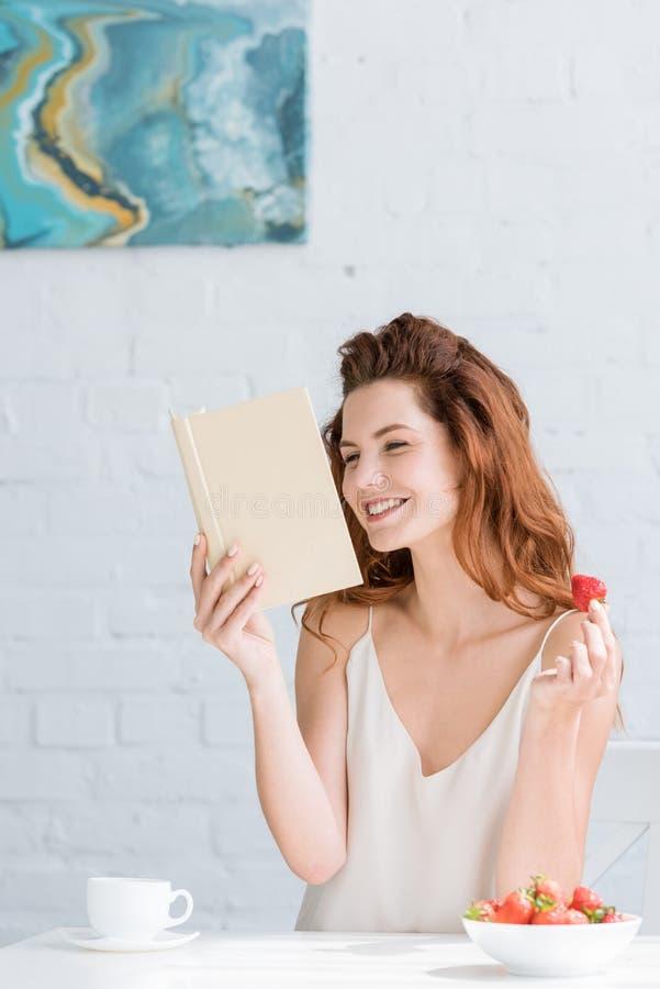 有咖啡和草莓看书的愉快的年轻女人 图库摄影