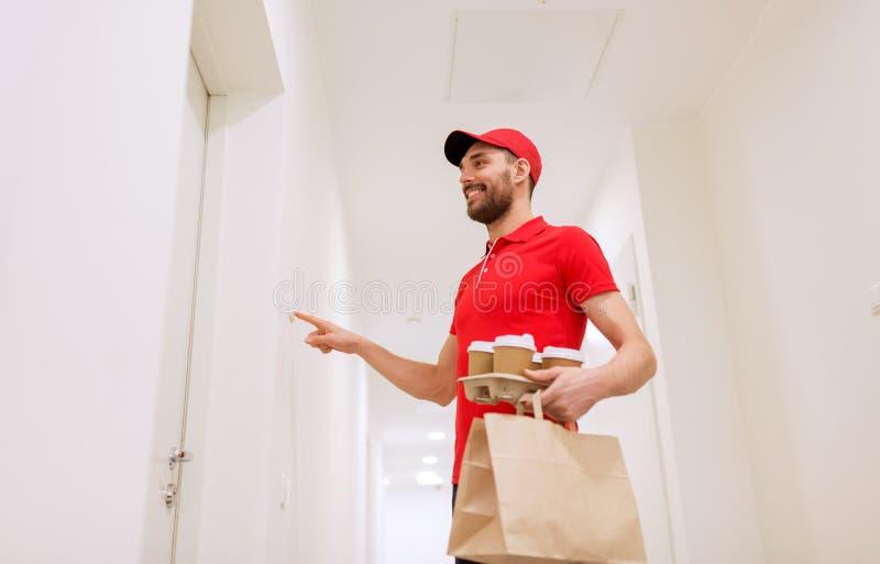 有咖啡和食物敲响的门铃的送货人 库存图片