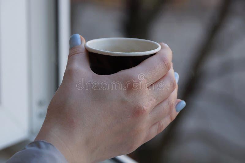 有咖啡在手中女孩的纸杯 图库摄影