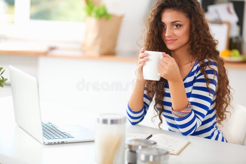 有咖啡杯和膝上型计算机的微笑的少妇在厨房里在家 免版税库存照片