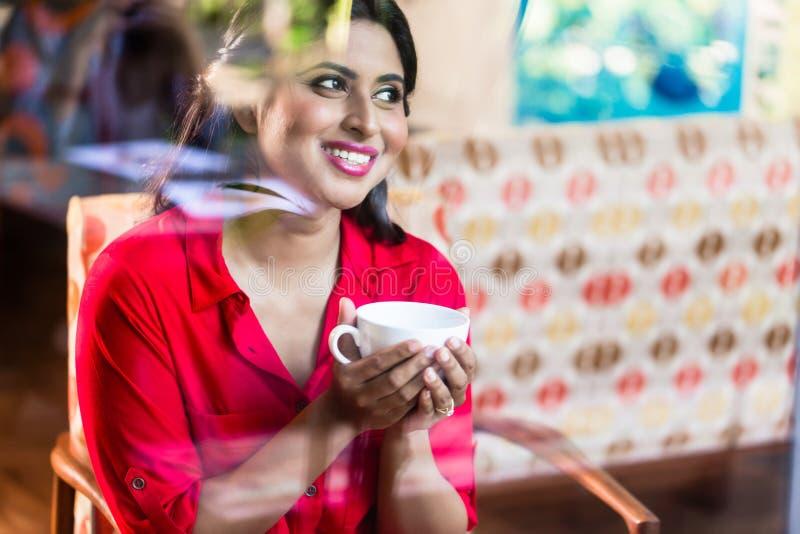 有咖啡杯的印地安妇女 库存照片