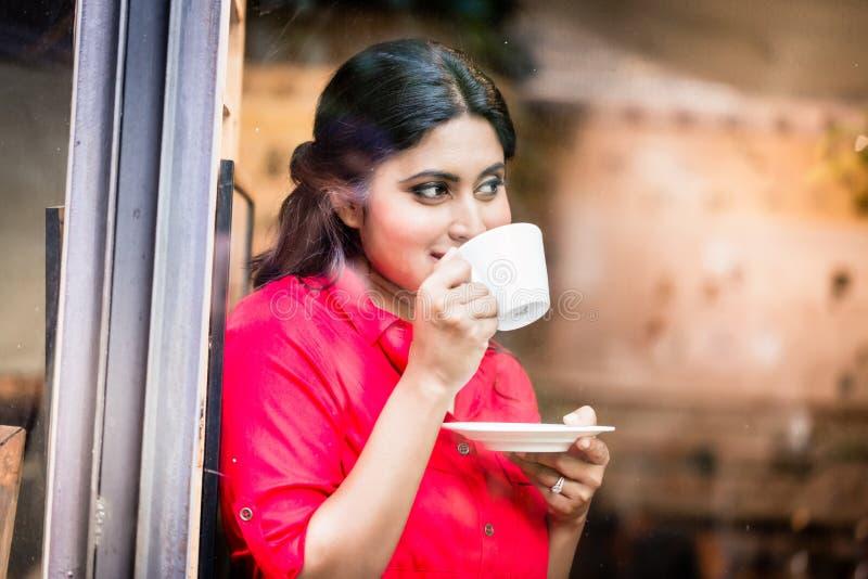 有咖啡杯的印地安妇女 免版税库存图片