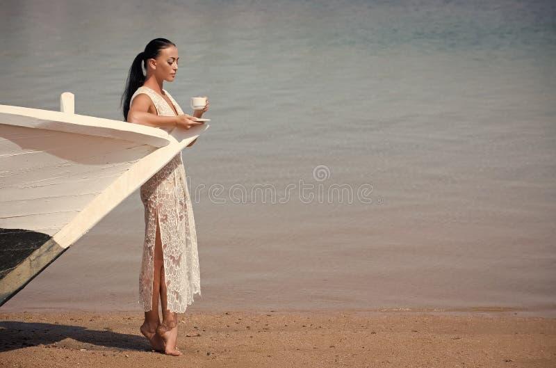 有咖啡杯的女孩在小船 免版税图库摄影