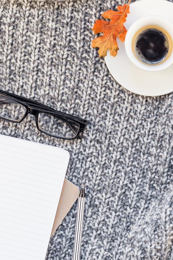 有咖啡杯的家庭工作场所在被编织的格子花呢披肩 库存照片