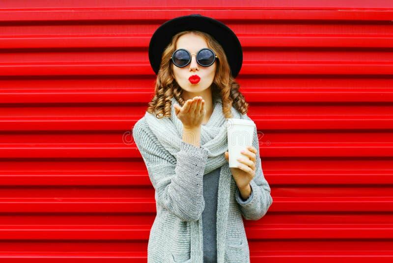 有咖啡杯的时尚画象俏丽的妇女吹红色嘴唇 免版税库存图片