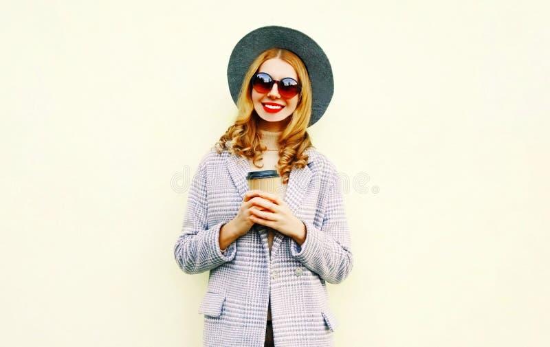 有咖啡杯的画象愉快的微笑的妇女在桃红色外套,在背景的圆的帽子 图库摄影