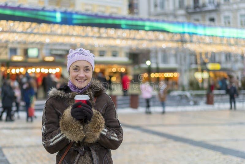 有咖啡杯的美丽的少妇在城市 美女用在街道上的咖啡在冬季衣服 有的妇女热 免版税库存照片