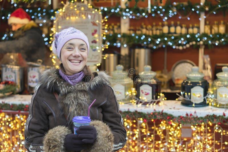 有咖啡杯的美丽的少妇在城市 美女用在街道上的咖啡在冬季衣服 有的妇女热 免版税库存图片