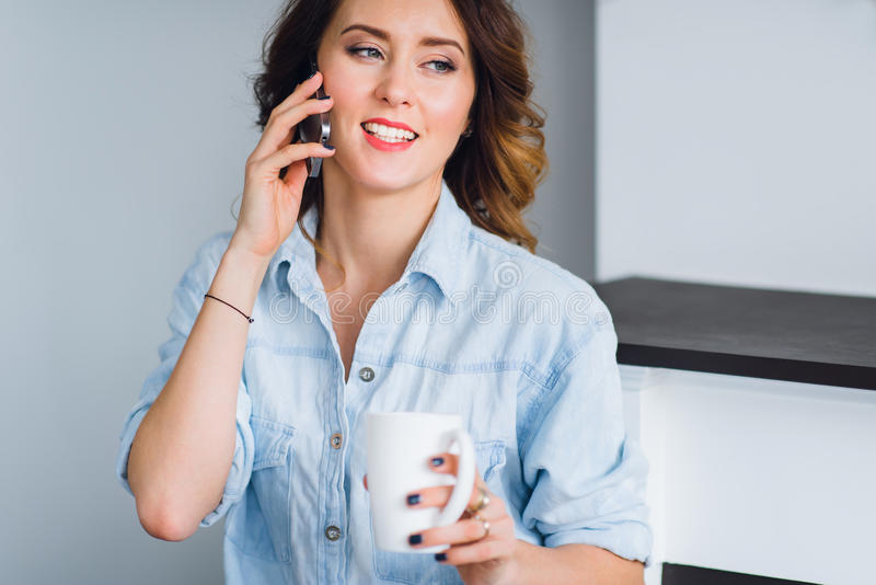 有咖啡杯的美丽的微笑的妇女在家谈话在手机 免版税库存照片