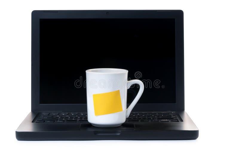 有咖啡杯的膝上型计算机 免版税库存图片