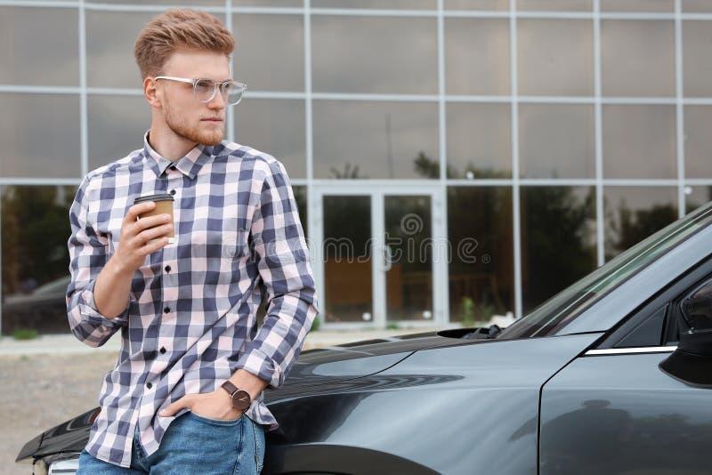 有咖啡的可爱的年轻人在豪华汽车附近的 图库摄影