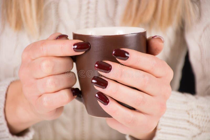 有咖啡的女孩和棕色指甲油 女服美丽的毛线衣 免版税图库摄影
