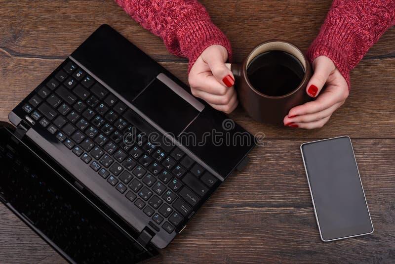 有咖啡的女性手和膝上型计算机有智能手机的在木背景 库存照片