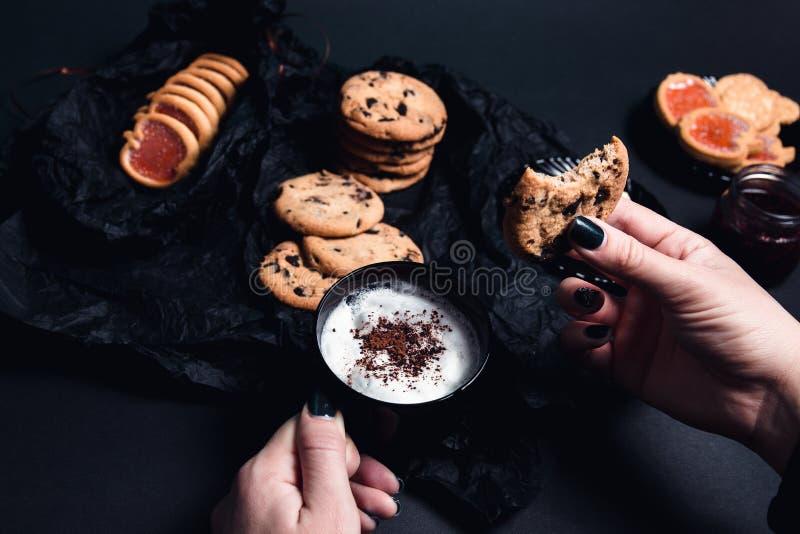 有咖啡的妇女手或热奶咖啡和巧克力曲奇饼,在黑桌背景的饼干 下午断裂时间 细分 免版税库存图片