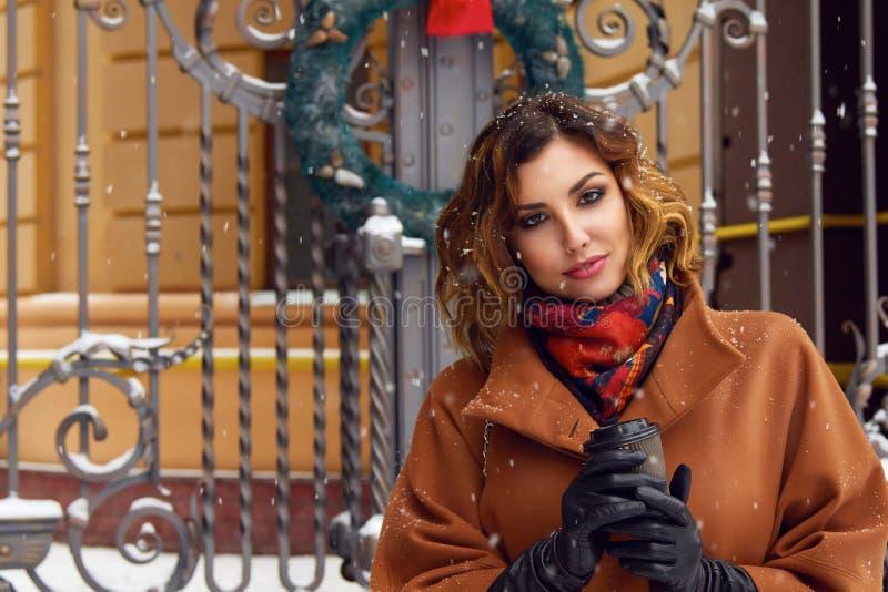 有咖啡的妇女步行在雪街道圣诞节新年 免版税库存照片