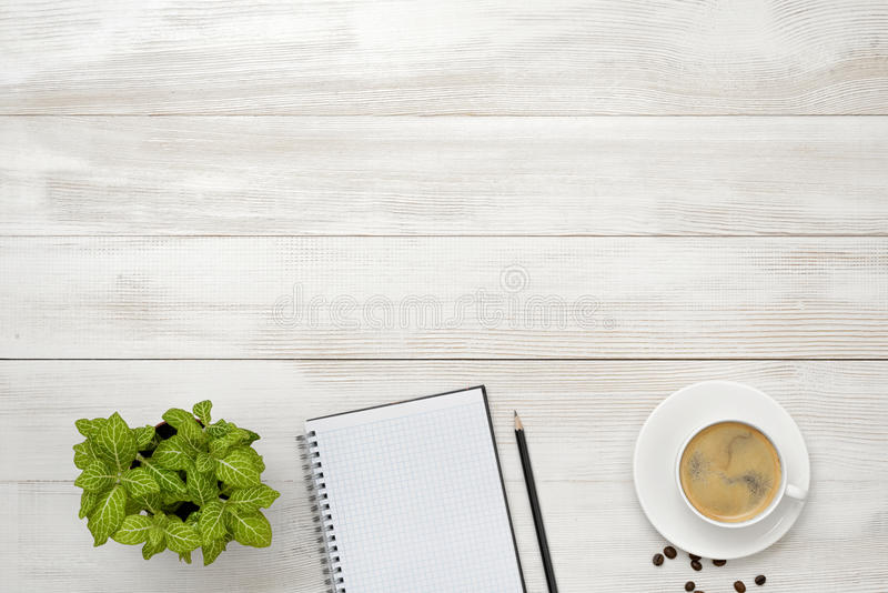 有咖啡的工作场所、室内植物、空的笔记本和铅笔木表面上在顶视图 库存照片