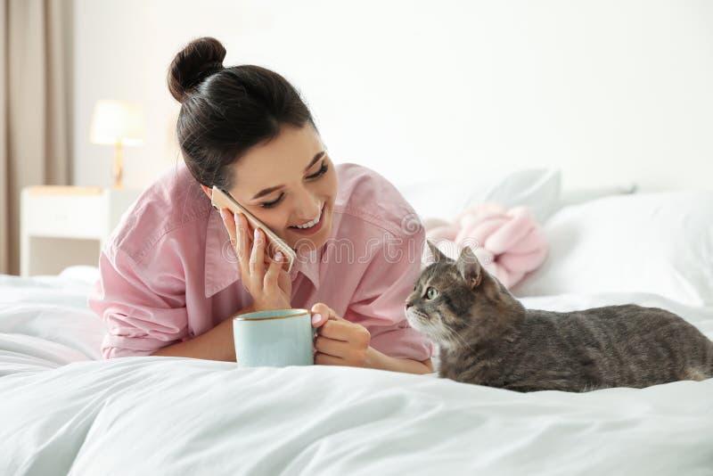 有咖啡的年轻女人谈话在电话,当说谎在逗人喜爱的猫附近在卧室时 免版税库存照片