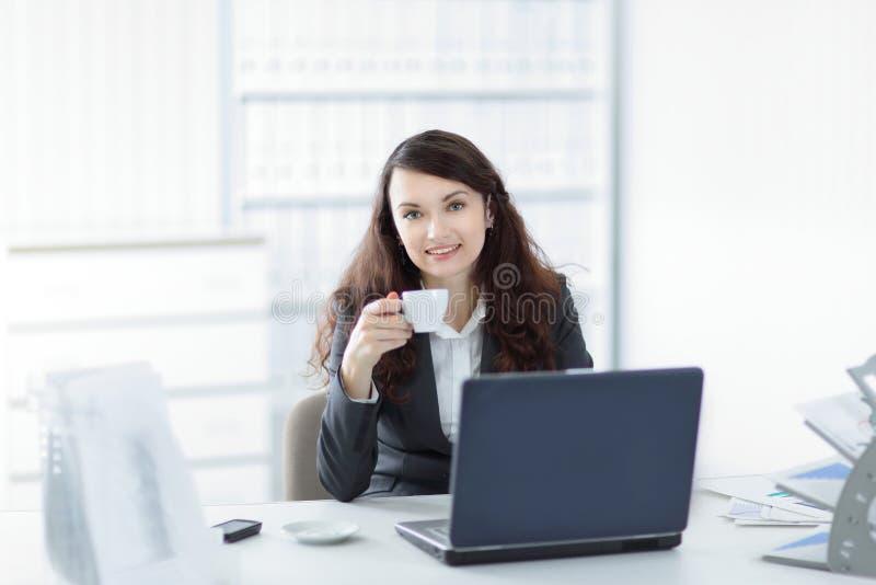 有咖啡的年轻女商人在工休的 免版税库存图片