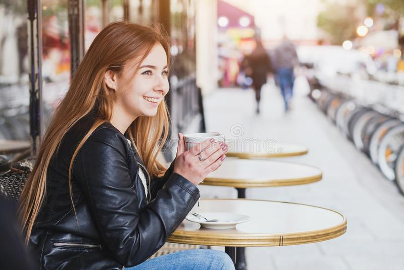 有咖啡的愉快的微笑的可爱的少妇在街道咖啡馆的 库存照片