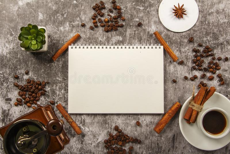 有咖啡的模板大模型干净的笔记本,咖啡粒,桂香,在灰色背景的磨咖啡器 在视图之上 La 库存图片