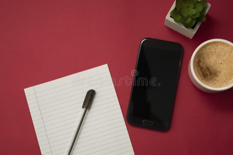 有咖啡的现代工作场所、智能手机、装饰植物多汁植物和笔 红色五颜六色的背景 事务和 免版税库存照片