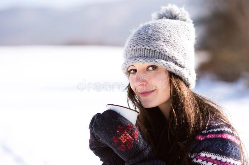 有咖啡的美丽的少妇在冬天自然的 免版税图库摄影