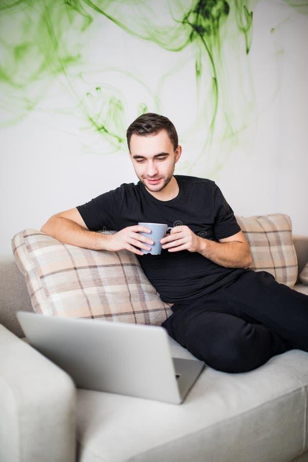 有咖啡的英俊的微笑的年轻人使用膝上型计算机的在家 图库摄影