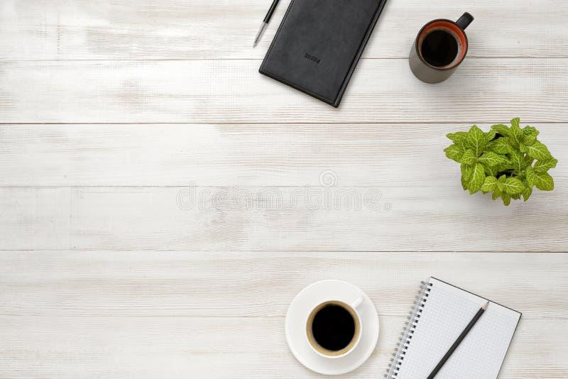 有咖啡的顶视图工作场所、盆栽植物、笔记本、铅笔和笔在木桌上 库存照片